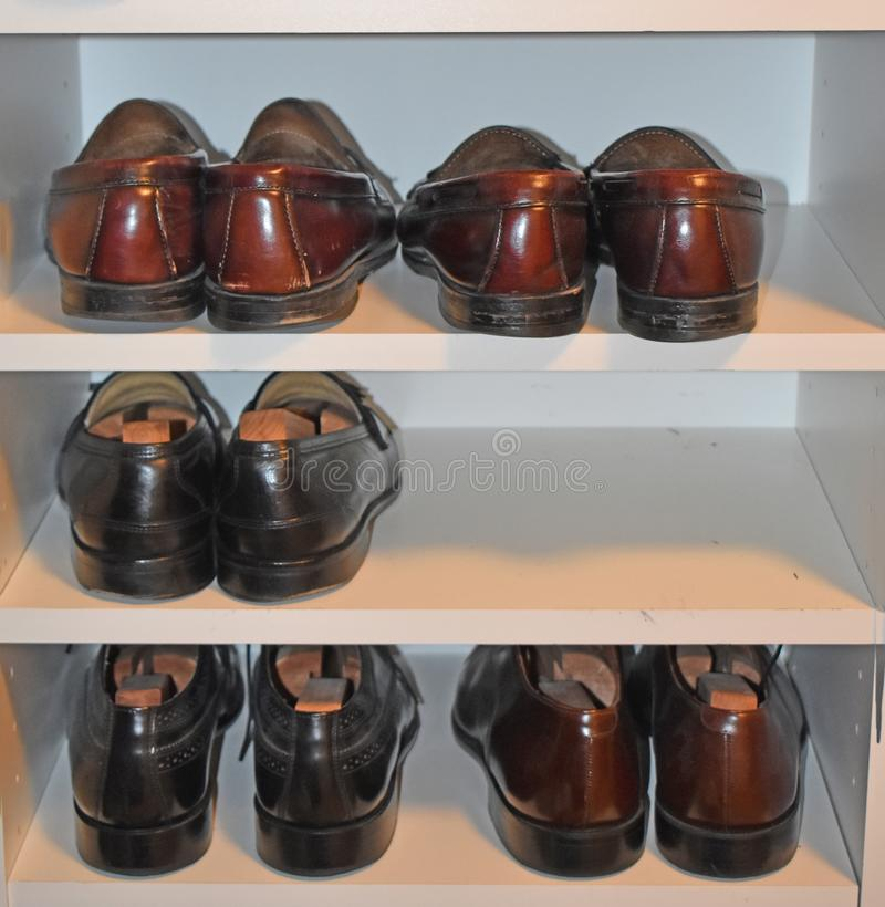 Shoes ready to wear in man`s closet. A man`s shoes are shined and ready to wear in a walk-in closet royalty free stock photography