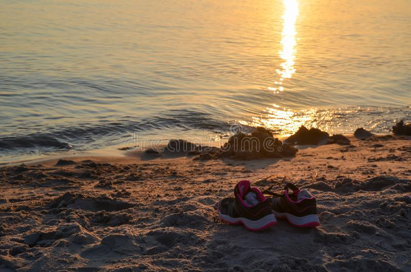 Shoes by seaside on a sandy beach. With sunset reflections in the water stock images