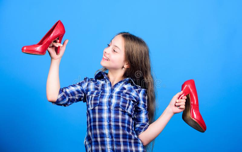Shoes shop. Happy childhood. Glamour high heels. Awesome red stiletto shoes. Little fashionista kid with high heels. Wish to grow up faster. Every girl stock photography