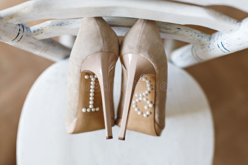 Shoes standing on chair. Pearls on sole. Closeup, point of view. No people, indoor, interior studio royalty free stock photography