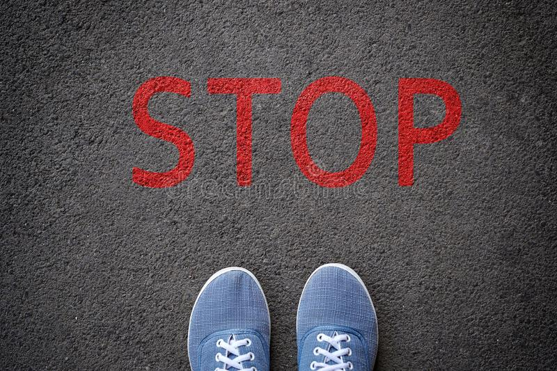 Shoes standing before stop sign painted on asphalt, top view royalty free stock photos
