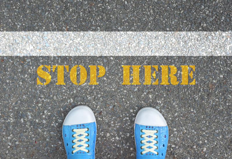 Shoes stop at stop line. Blue shoes standing behind the white line with yellow stop here sign royalty free stock photography
