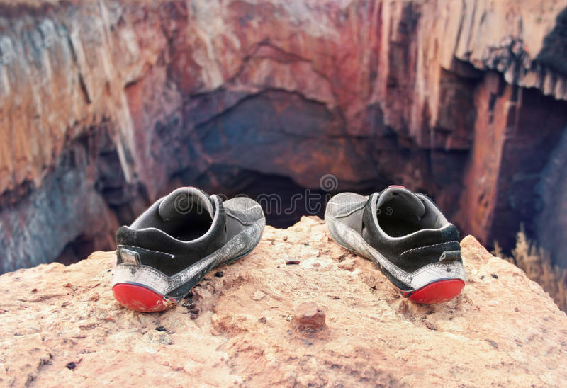 Shoes of the suicide. Shabby old shoes of the suicide on the brink of a precipice stock photos