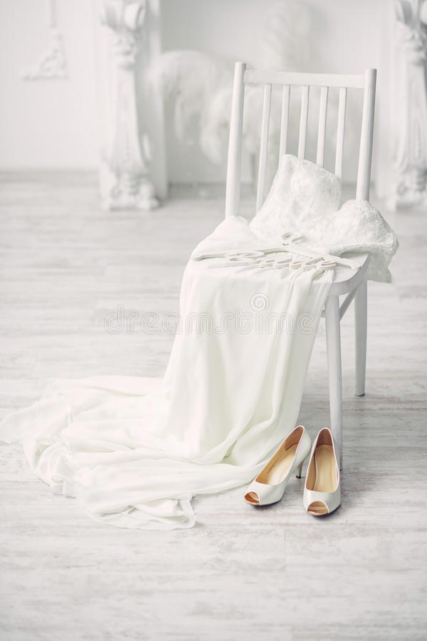 Shoes and wedding dress on chair in room stock photography