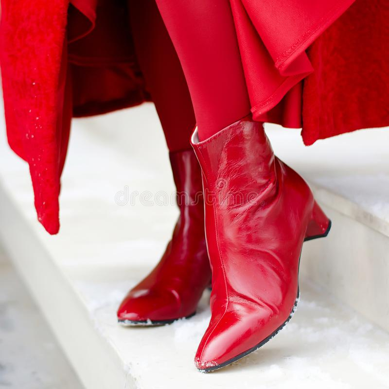 Shoes woman. beautiful boots on women`s legs. red shoes close-up outdoors. happy woman royalty free stock photo