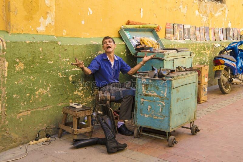 Shoeshiner в Колумбии жаждая для клиента стоковое изображение