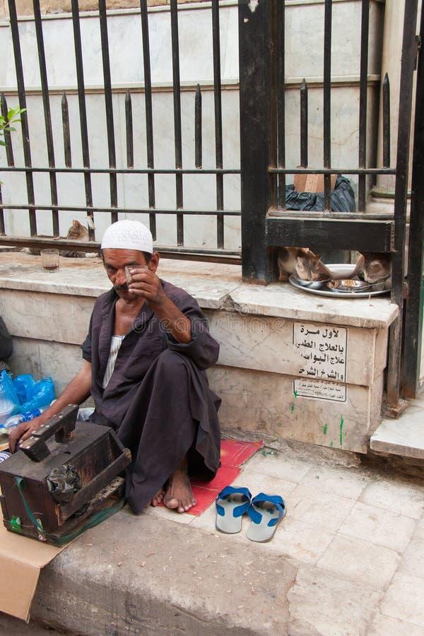 Shoeshiner het drinken thee en katten die op de achtergrond in s eten royalty-vrije stock afbeeldingen