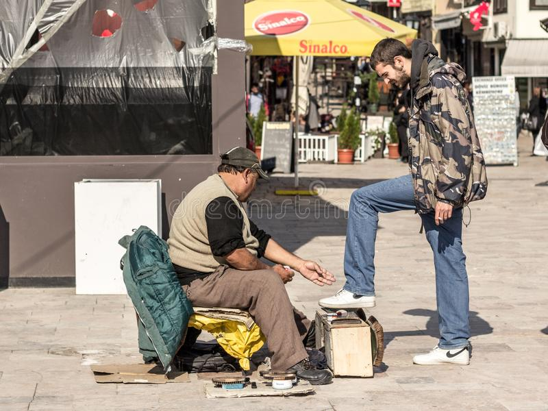 Shoeshiner polishing the shoes of a white young man in the Skopje bazar in the capital city of Macedonia royalty free stock photography