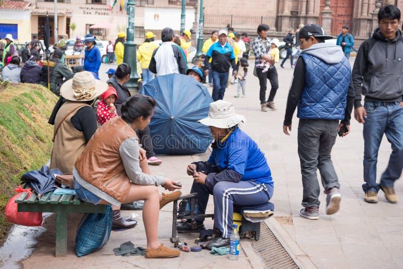 Shoeshiner que trabalha na rua de Cusco, Peru imagens de stock royalty free