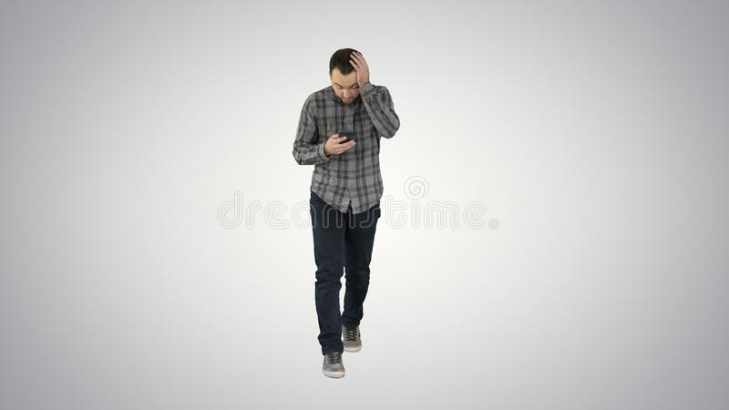 Shoked young man holding phone and reading message when walking on gradient background. royalty free stock images