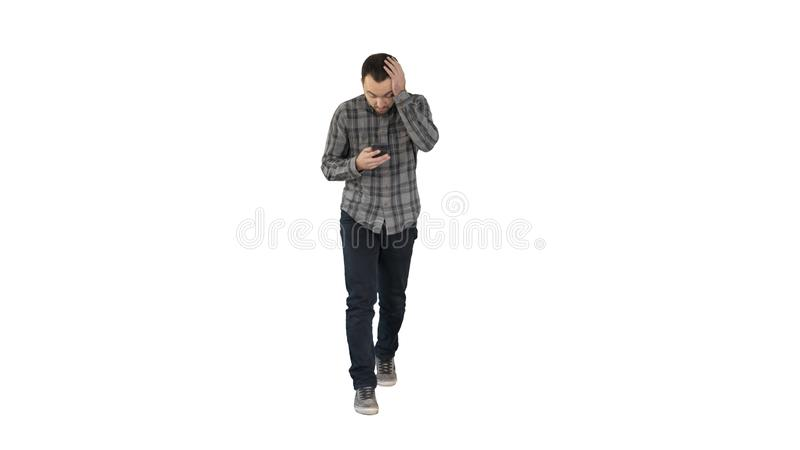 Shoked young man holding phone and reading message when walking on white background. stock photography