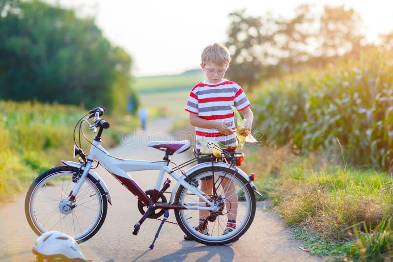 Shool ungepojke som har gyckel med ridning av cykeln arkivbild