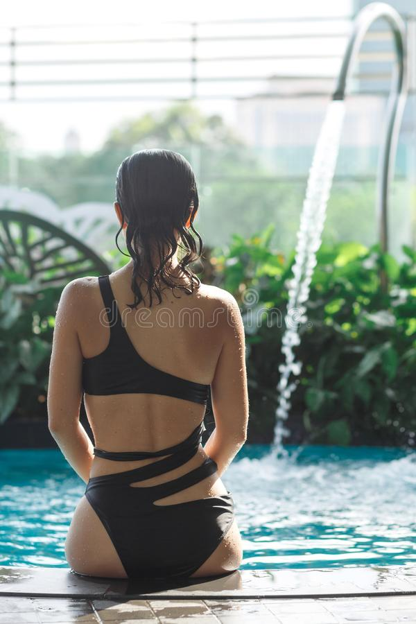 Shoot from back of sexy slim female in swimsuit sits on edge of swimming pool between green bushes on rooftop with city scape stock images