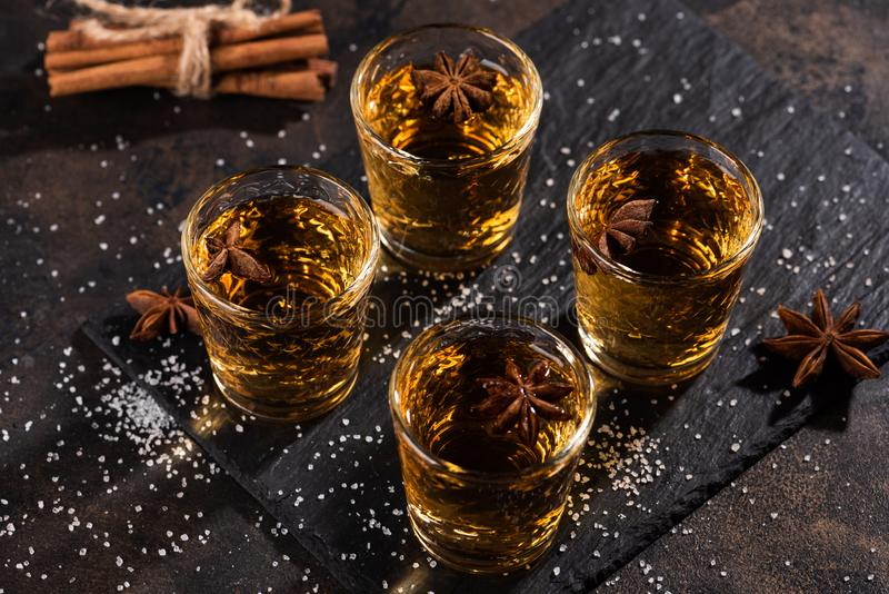 Shoot glass of alcoholic drinks with star anise, cinamon and salt. On metal table and black stone tray royalty free stock images