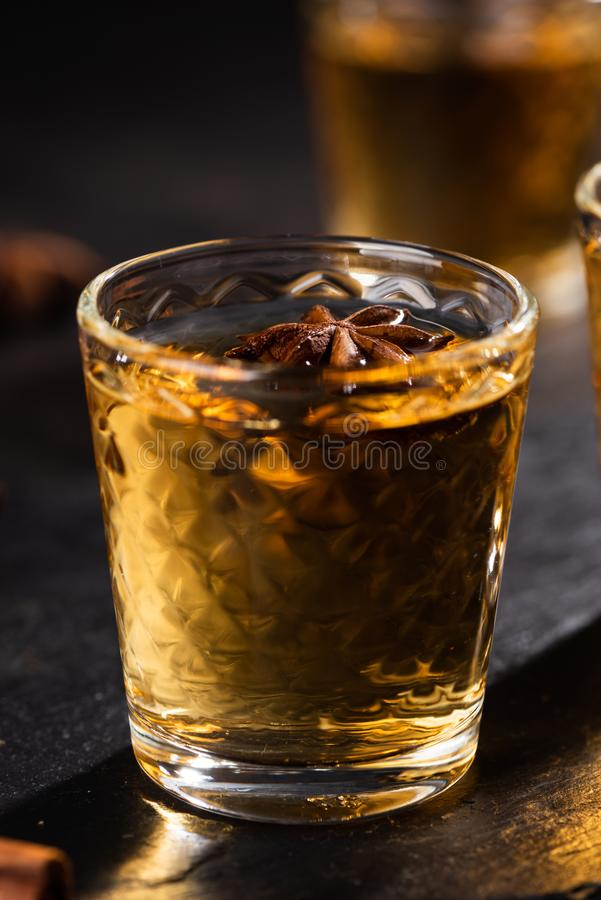 Shoot glass of alcoholic drinks with star anise, cinamon and salt. Shoot glass of alcoholic drinks with star anise and cinamon on metal table and black stone stock photo