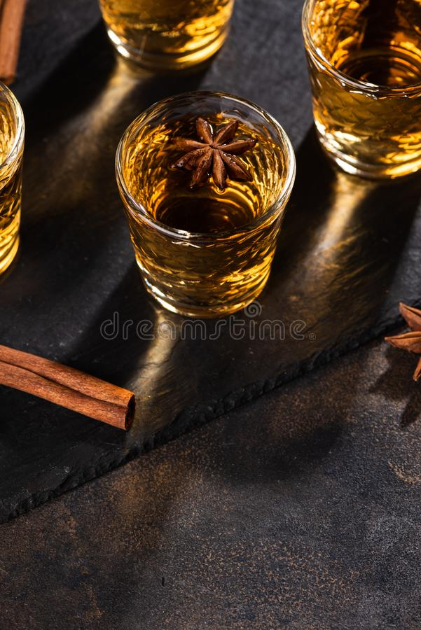 Shoot glass of alcoholic drinks with star anise, cinamon and salt. Shoot glass of alcoholic drinks with star anise and cinamon on metal table and black stone royalty free stock photography