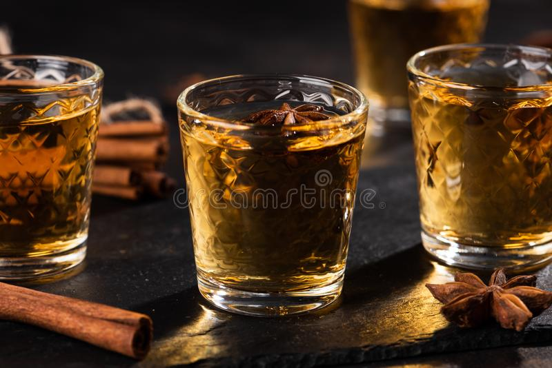 Shoot glass of alcoholic drinks with star anise and cinnamon. On metal table and black stone tray stock photos