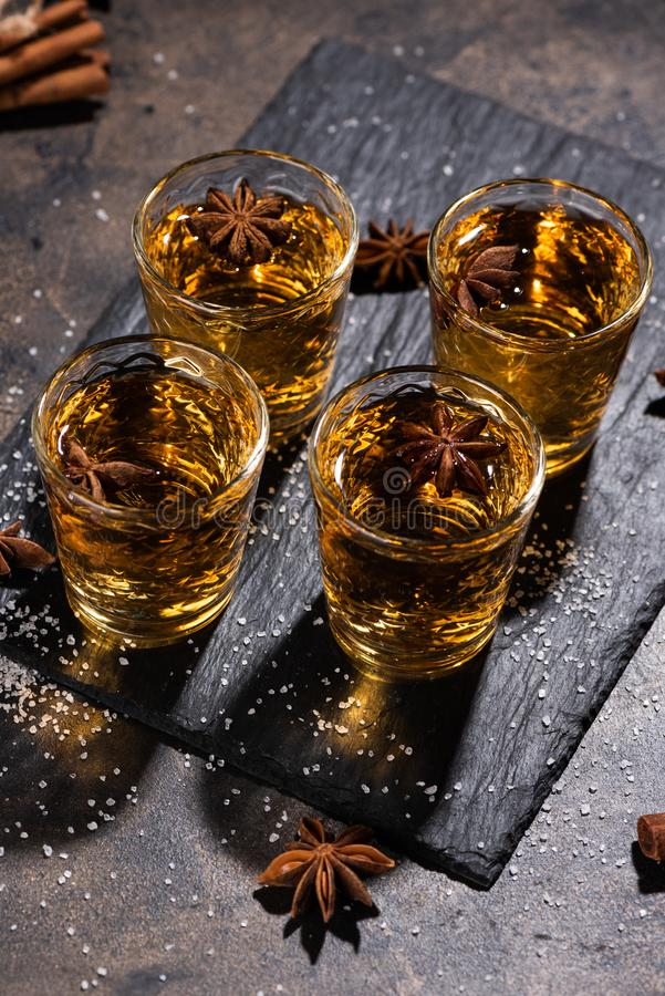 Shoot glass of alcoholic drinks with star anise and cinnamon. Shoot glass of alcoholic drinks with star anise, cinamon and salt on metal table and black stone royalty free stock image