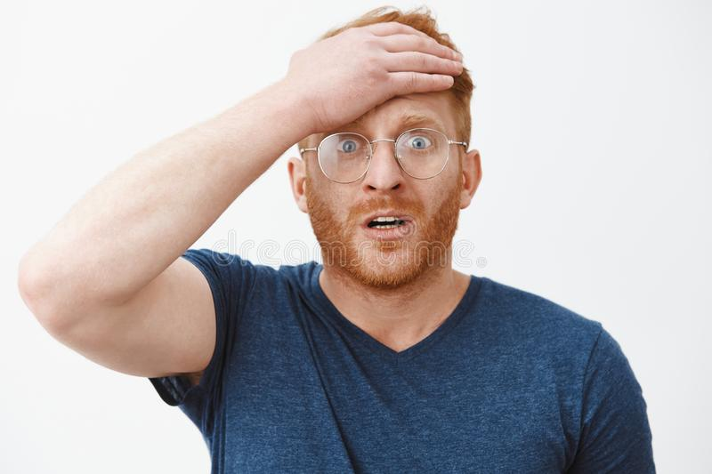 Shoot I forgot about anniversary. Portrait of worried forgetful cute redhead husband with beard holding palm on forehead royalty free stock photo
