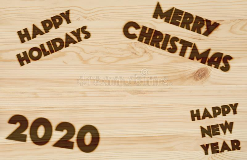 Merry Christmas and Happy New Year 2020 Background. Burned in wood royalty free stock photo