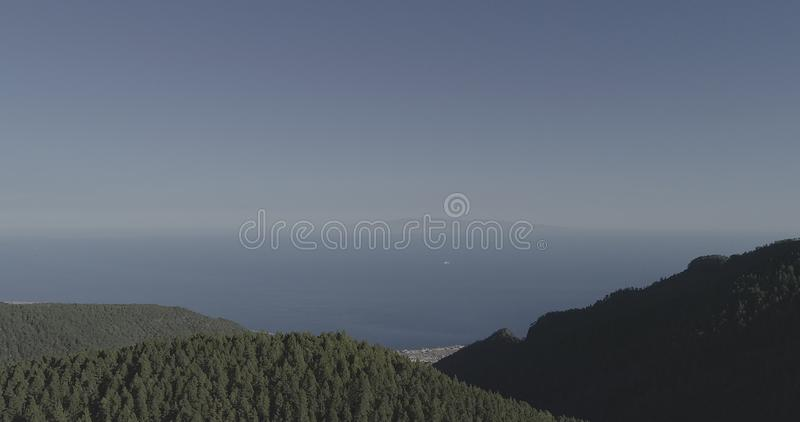 A boat between two islands. Shooted by drone you can see the forest Tenerife and La Gomera royalty free stock photo