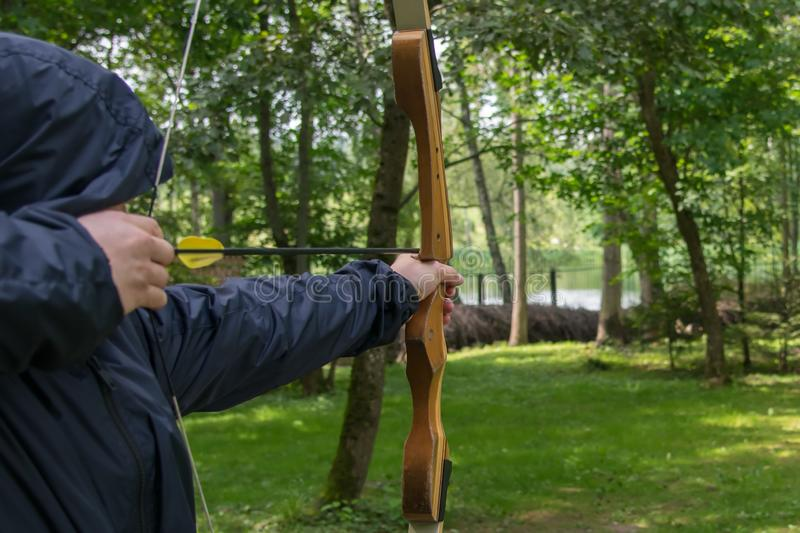 The shooter in the blue hood, pulls the bow string, to hit the target royalty free stock photo