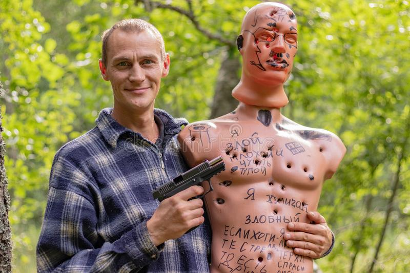 The shooter is holding a mannequin with bullet holes. Dummy as a target when shooting from a traumatic pistol stock photography