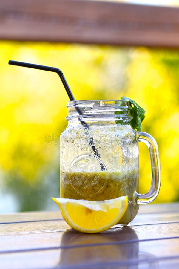 Shoothie fresco del limone in barattolo con paglia sulla tavola di legno fotografia stock libera da diritti