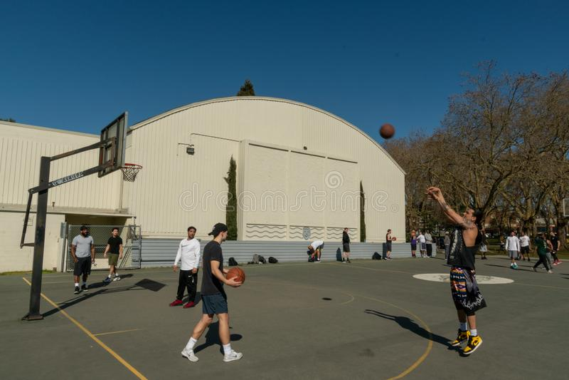 Shooting basketball at hoop. Seattle, Washington - 2019-03-17 - Man shooting ball at basketball hoop in Greenlake as Spring begins in Seattle stock photos
