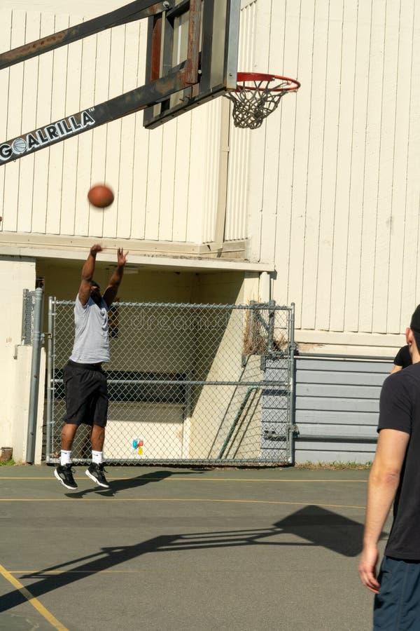 Shooting basketball at hoop. Seattle, Washington - 2019-03-17 - Man shooting ball at basketball hoop in Greenlake as Spring begins in Seattle royalty free stock image