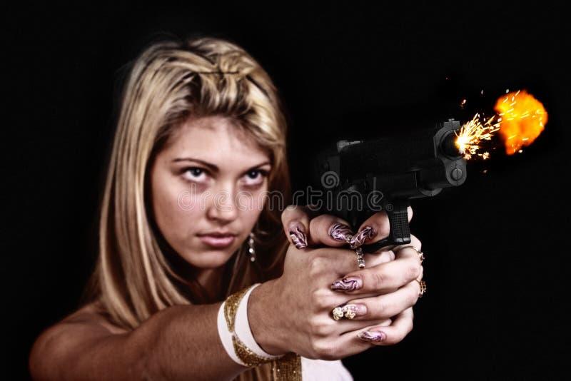 Shooting de la mujer joven con la pistola. fotos de archivo libres de regalías