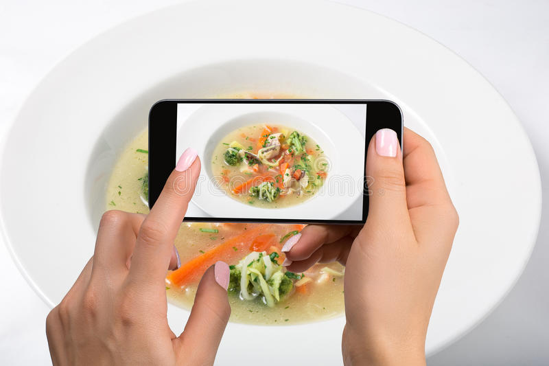 Shooting food on phone`s camera. Chicken soup with broccoli, carrots and celery in a white bowl on a white background. royalty free stock photography