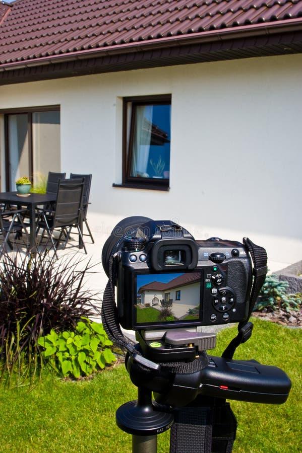 Shooting house exterior, photographer camera, tripod and ballhead stock images