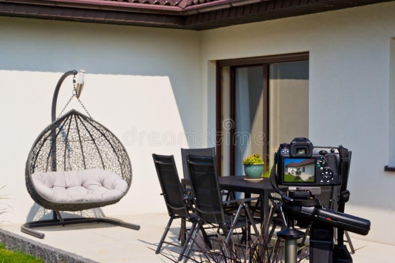 Shooting house exterior, photographer camera, tripod and ballhead stock photography