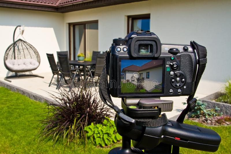 Shooting house exterior, photographer camera, tripod and ballhead stock image