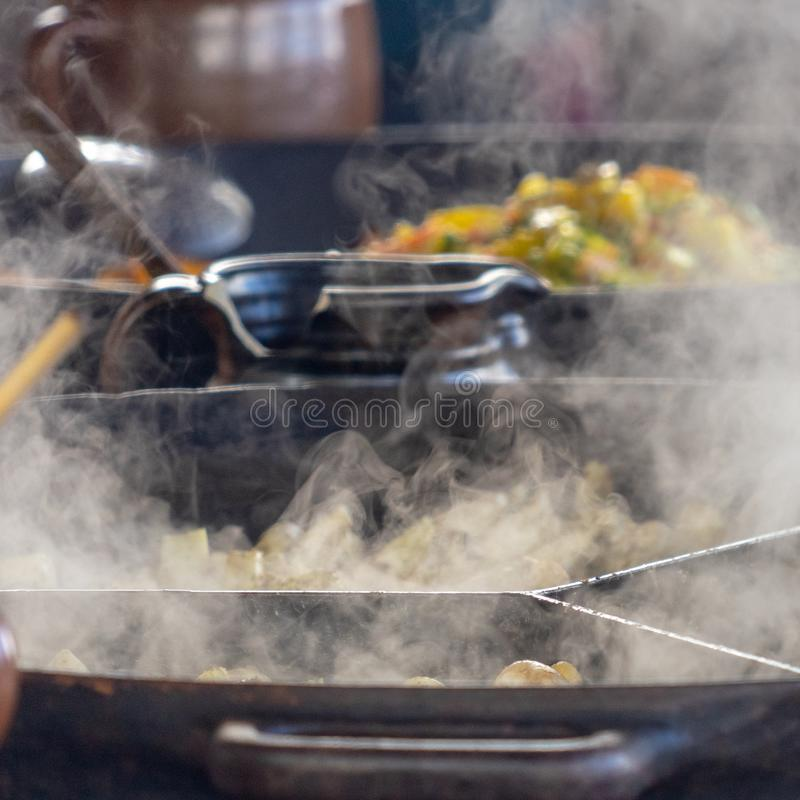 Shooting of large steaming pans, steam in the foreground focused, vegetable pan in the background deliberately blurred stock image