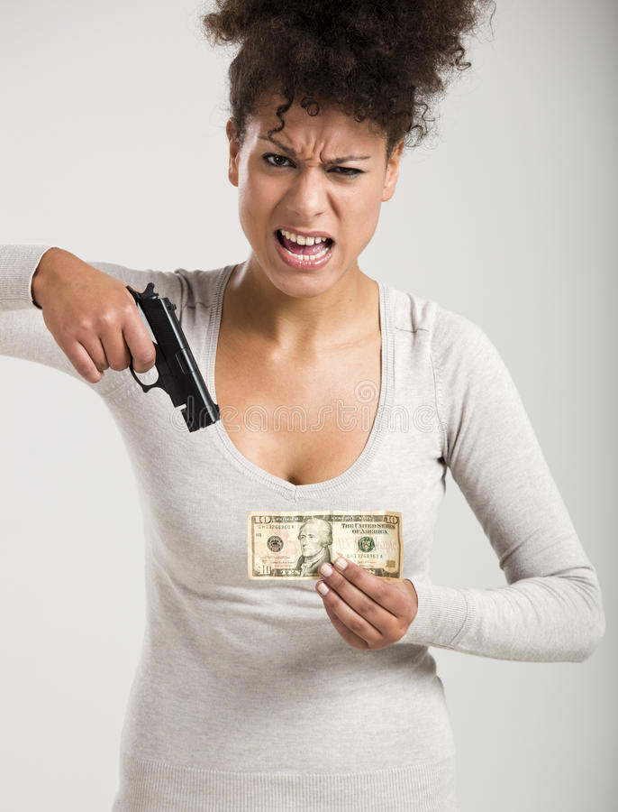 Shooting money. African woman shooting a US-Dollar banknote, great concept for the global crises stock photography