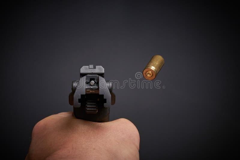 Shooting the pistol. Firing a handgun, flying empty shell stock image