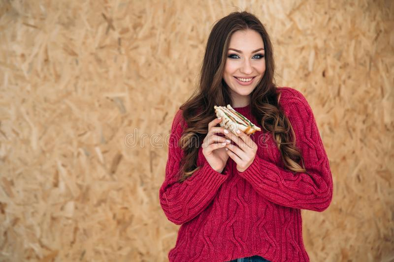 Shooting sideways a young cheerful girl with a beautiful smile in a modern cherry-colored sweater wants to eat her. Breakfast before work, holds a sandwich with stock photo