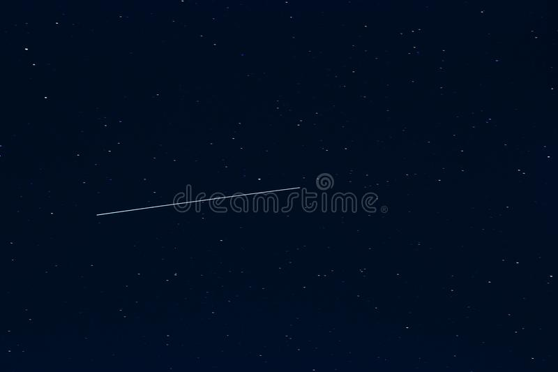 Shooting star against dark blue starry night sky royalty free stock image