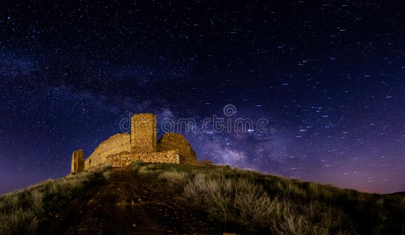 Shooting stars attack a lonely castle on top of a hill. stock photos