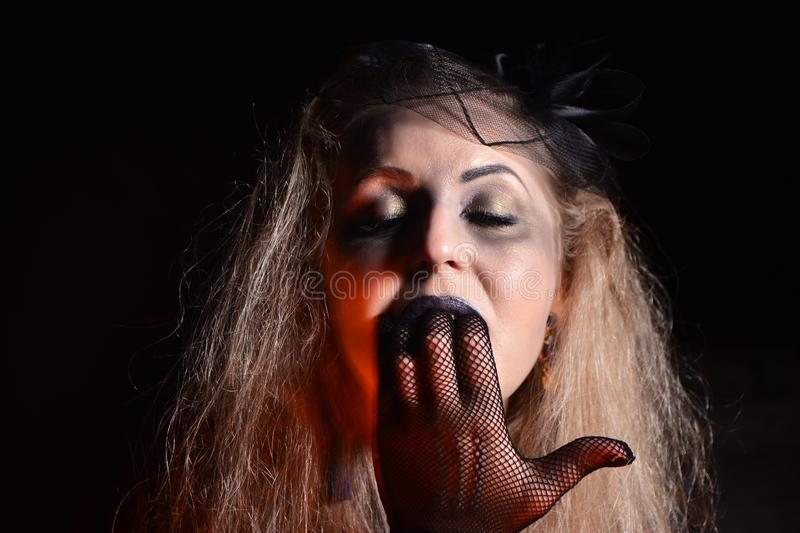 Shooting a thematic fashion portrait. Hands in checkered gloves. Fingers in the girl`s mouth. Portrait of a witch for Halloween party announcement royalty free stock photography