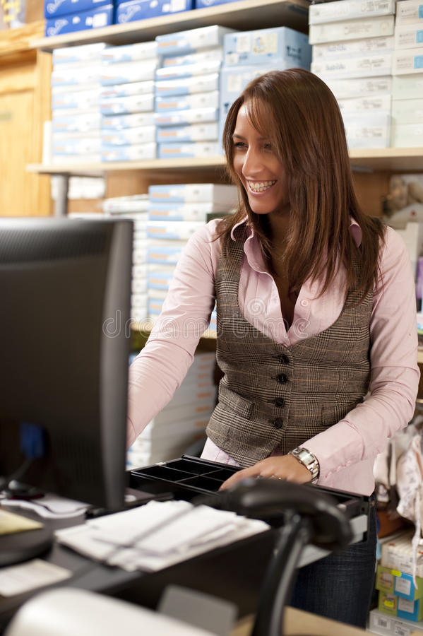 Shop assistant at cash stock images