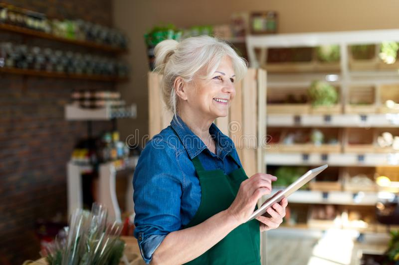 Shop assistant with digital tablet in small grocery store royalty free stock images