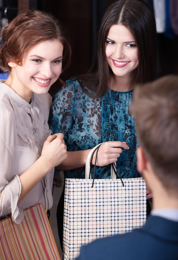 Shop assistant gives a piece of advice to clients royalty free stock photos