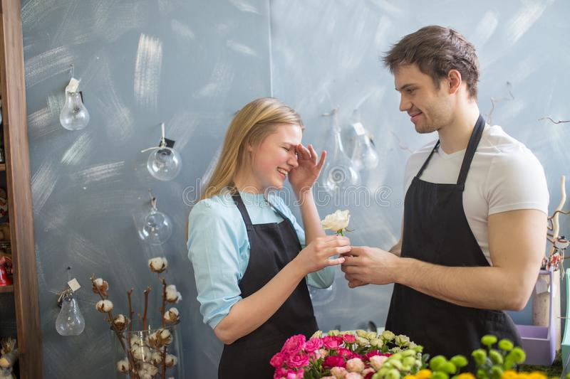 Shop assistant giving flower to his embarrased collegue royalty free stock image