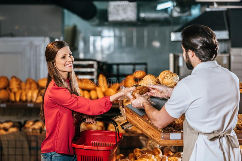 shop assistant giving loaf of bread to smiling woman stock photos