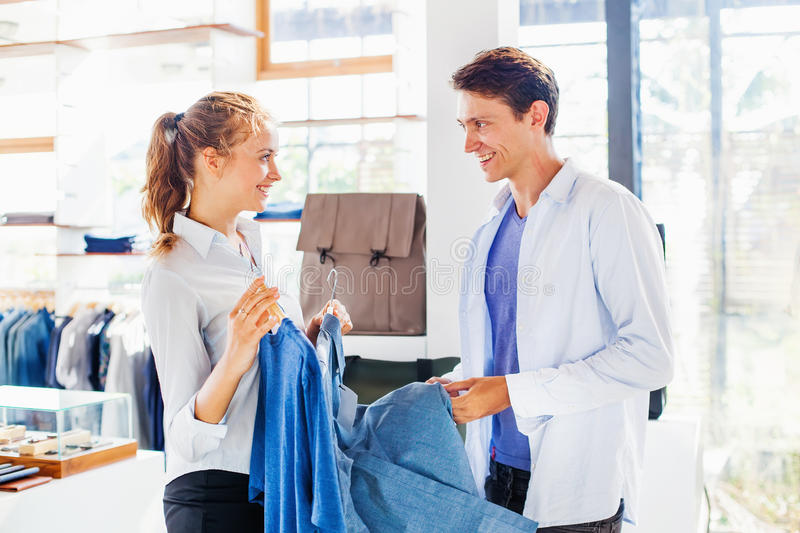Shop assistant helping to choose clothes royalty free stock photos