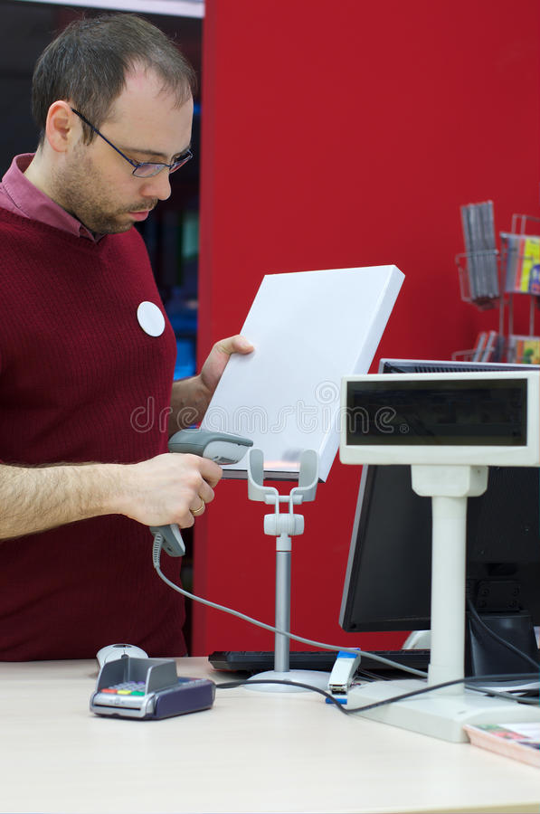 Shop assistant male scanning a book stock photos