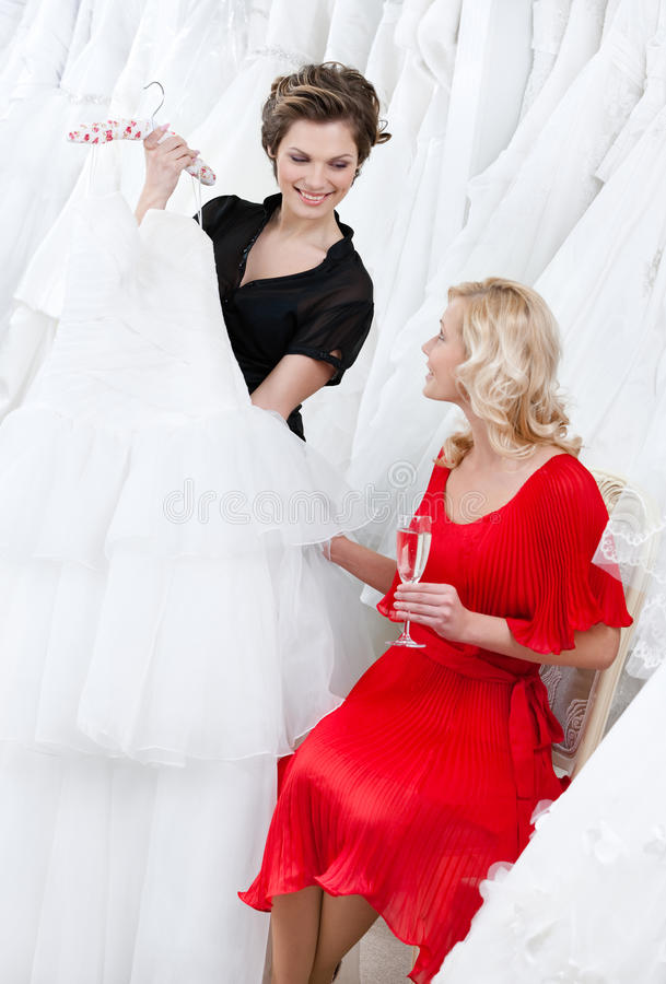 Shop assistant offers another dress to the bride stock photo